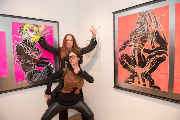 Two of Jo's Rubber Angels, Isabelle Bricknall and Eryka Isaak, beside their portraits